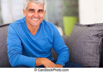 mature man relaxing at home - smiling mature man relaxing at...