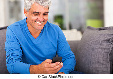 middle aged man reading emails on smart phone - cheerful...