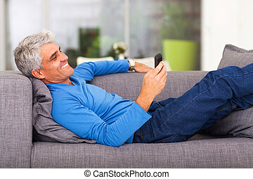 middle aged man reading text message on mobile phone while...