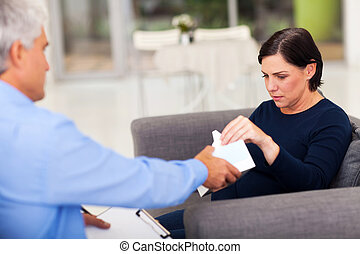 therapist handing tissue to an upset middle aged patient -...