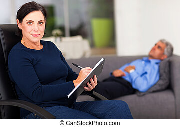 portrait of middle aged female therapist in office with...