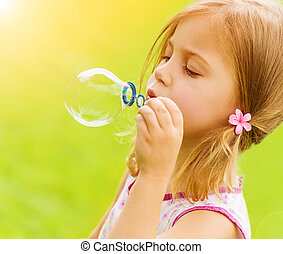 Little girl blowing soap bubbles - Sweet little girl blowing...