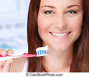 Woman brushing her teeth - Closeup portrait of beautiful...