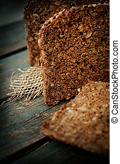 Rustic loaf of bread with sunflower seeds on wood background