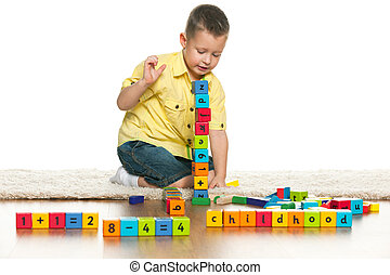 Clever preschool boy is playing with toys