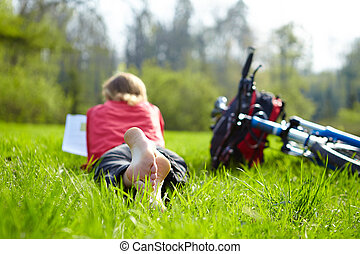 Girl cyclist on a halt reads on green grass outdoors in...