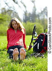 Girl cyclist barefoot enjoying relaxation sitting in green...