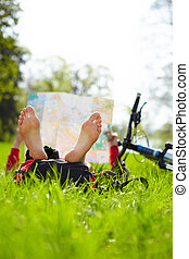 Cyclist on a halt reads a map lying on green grass in spring park