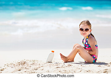 Sun protection - Little girl with bottle of sun cream...