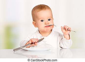Funny baby with a knife and fork eating food - Funny happy...