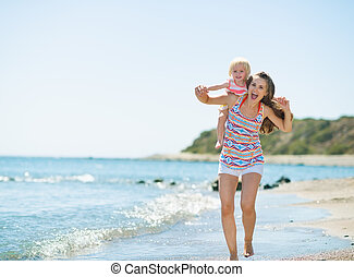 Happy mother holding baby on back and running along sea...