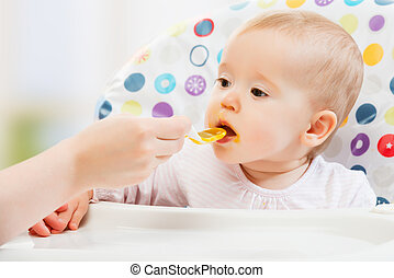 Mom feeds funny baby from spoon - Mom feeds funny baby from...