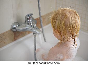Baby washing in foamy bathtub
