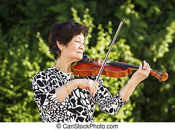 Horizontal photo of Senior Asian woman focused, with her eyes closed, while playing the violin outdoors with bright green trees in background
