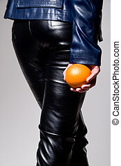 The girl in black leather pants with an orange in his hand...