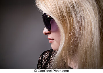 Profile of a woman in sunglasses on a gray background
