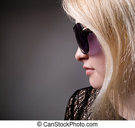 Profile of a woman in fashion sunglasses on a gray...