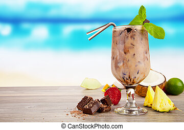 Summer cocktail with pieces of fruit on wooden table. Blur beach on background