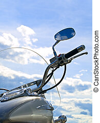 motorcycle handle bar against blue cloudy sky