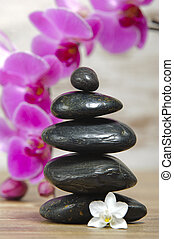 Japanese zen garden with stacked stones and orchid flower