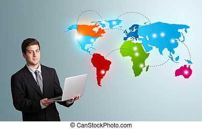 young man holding a laptop and presenting colorful world map