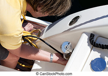 Man Connecting Power Cord To The Boat - Man connecting power...