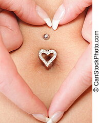 hands heart symbol around navel piercing - woman's hands...