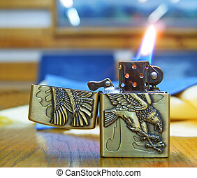 Lighter with Flame - A cigarette lighter with a yellow and...