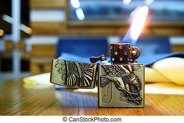 Lighter with Flame on the table - A cigarette lighter with a...