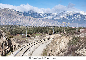 Rail road. At the background, snow capped peaks of the...