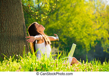 Beautiful young woman relaxing on grass with laptop