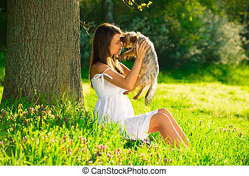 Cute woman with dog in nature