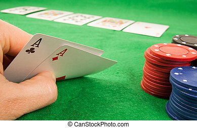 A pair of aces in a hand with a stack of chips and cards on...