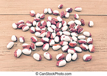 Pile green calypso beans on wooden board