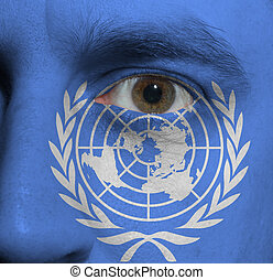 face with the United Nations flag painted on it - close-up...