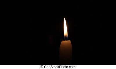 Candle with black background - A candle burns against a...