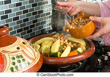 Tajine meal with chickpeas - Moroccan woman adding chickpeas...