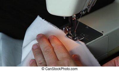 Woman hand guiding white cloth thro