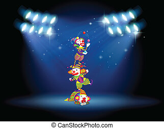 Three clowns performing on the stage with spotlights -...