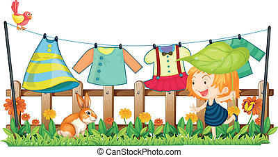 A child and a bunny near the hanging clothes
