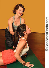 Yoga and Women - Women working together in class doing yoga