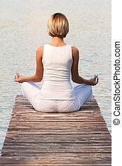 Young woman yoga on the lake