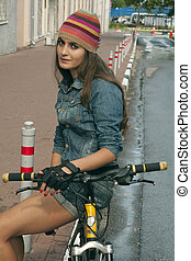 girl in knit hat with yellow bike