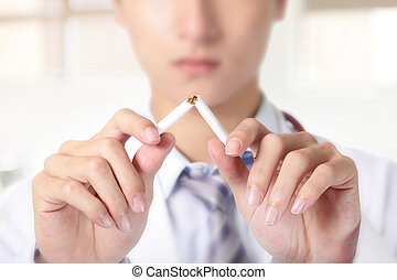 Quit smoking, doctor hands breaking the cigarette, close up,...
