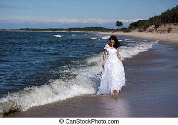 young girl walking along the seashore