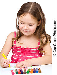 Little girl is drawing using colorful crayons