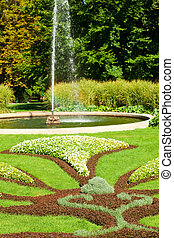 fountain in the park on a background of green grass