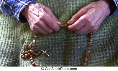 Old man praying rosary - Old wrinkled skin hands hold wooden...