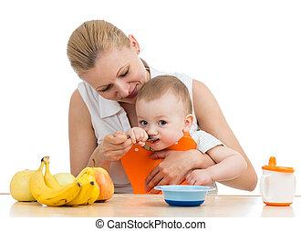 mother spoon feeding baby boy