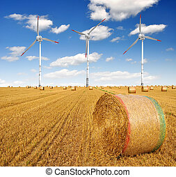 Straw bales on farmland with wind turbine on blue cloudy sky...